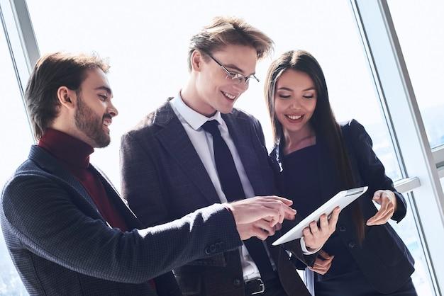 Бизнесмены и бизнес-леди в офисе, работая вместе, стоя обсуждают новое приложение на цифровом планшете, улыбаясь веселым крупным планом