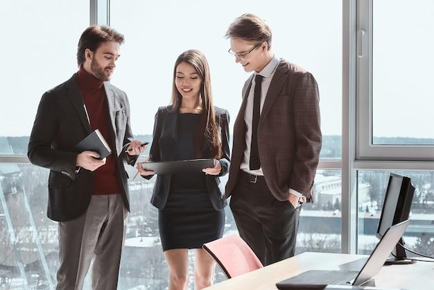 Бизнесмены и деловая женщина в офисе, работая вместе, стоя, глядя на держателя бумаги на плане проекта, улыбаясь, весело довольны стратегией