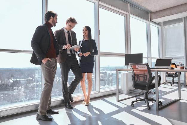 Бизнесмены и деловая женщина в офисе, работая вместе, стоя человек, опираясь на окно, просматривая цифровой планшет, сосредоточены, в то время как коллеги смотрят на него, радостно улыбаясь