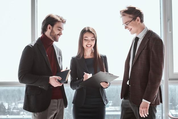Бизнесмены и деловая женщина в офисе, работая вместе, стоя мужчины, глядя на женщину, делающую заметки о проекте, улыбаясь счастливым