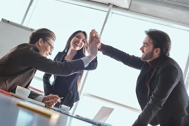 ビジネスマンとオフィスの実業家が一緒に立ってハイタッチ笑顔の陽気な成功したプロジェクトを与える