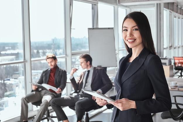 一緒に働いているオフィスのビジネスマンと実業家女性がクローズアップを見てカメラを笑顔で元気にデジタルタブレットを保持している間、同僚が座ってドキュメントを真剣に見て