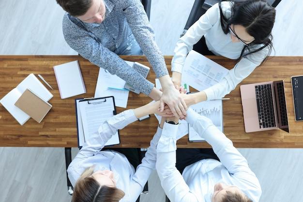 Бизнесмены и деловая женщина за рабочим столом держатся за руки. партнерство