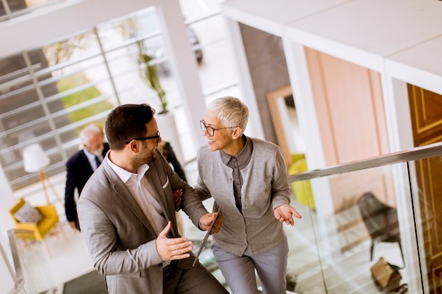 Бизнесмены и предприниматели гуляют и берут лестницы в офисном здании
