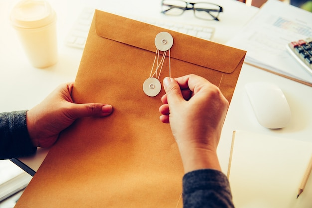 Businessmen are about to open a brown envelope containing business documents