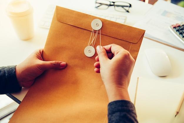 사업가는 비즈니스 문서가 들어있는 갈색 봉투를 열려고합니다