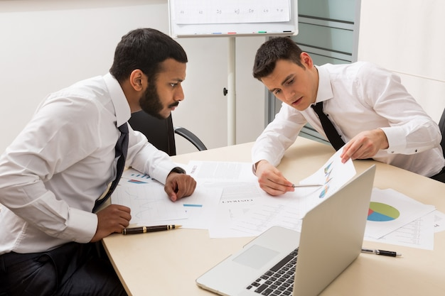 ビジネスマンはプロジェクトの成功した若い男クリエイティブマネージャーについて積極的に話し合っています