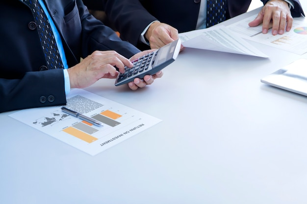 Businessmen are deeply reviewing a financial reports for a return on investment or investment risk analysis on a white desk. lower right copy space included.