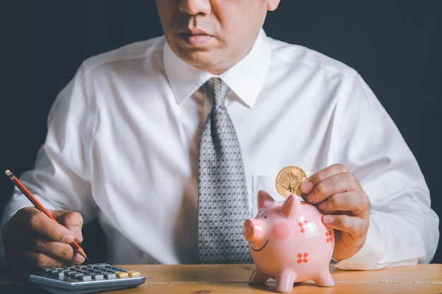 사업가들이 골든 비트 코인으로 돼지 저금통을 떨어 뜨리고 있습니다.