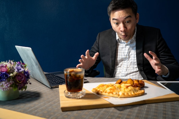 Businessmen are eating pizza and bbq chicken legs on the desk.
