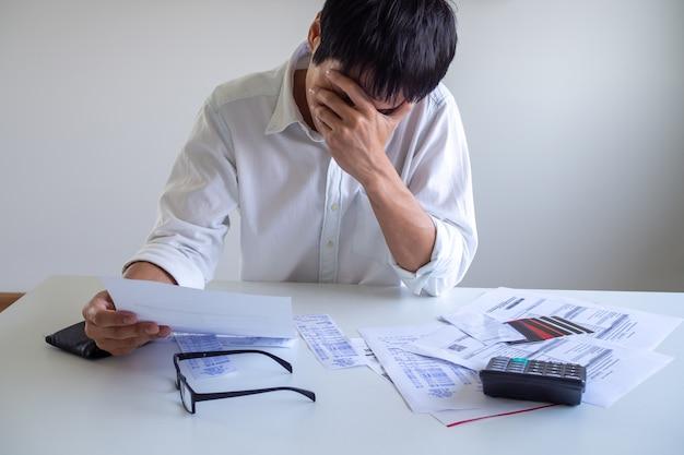 ビジネスマンは借金とクレジットカードの借金の問題でストレスと頭痛を抱えています。