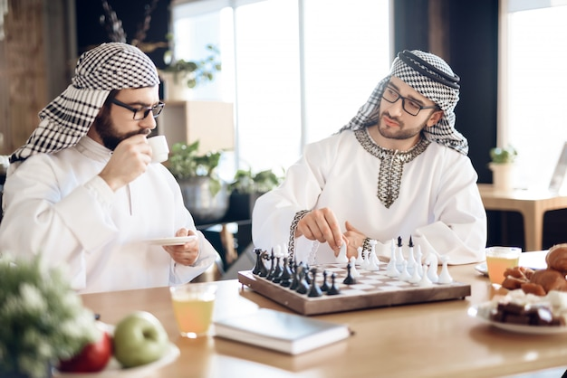 Businessmen are playing chess at table at hotel room.