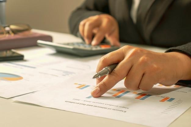 ビジネスマンは、レポート、財務データ分析のための財務文書、作業アイデア、および市場データを確認しています。