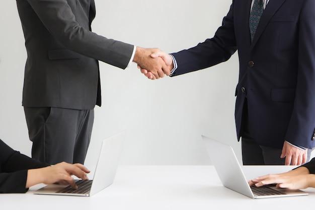 기업인들은 데이터를 분석하고 상황을 평가하고 노트북 컴퓨터를 사용하여 비즈니스의 위험을 함께 평가하는 양측 비서와 악수하고 있습니다.