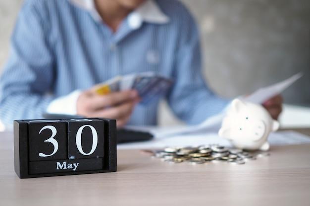 ビジネスマンは、月末にクレジットカードの支払いが必要だと強調しています。