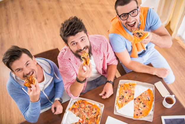 Businessmen are useing computers in office and eat pizza.