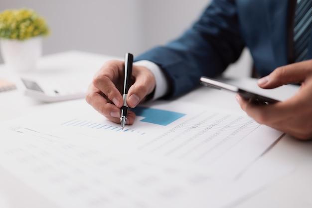 ビジネスマンは携帯電話を使用してインターネット情報を取得し、財務報告を監査しています