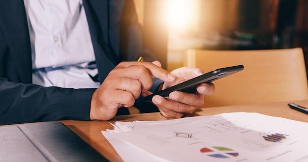 ビジネスマンは、モバイルとタッチのスマートフォンを使用して通信し、オフィスバックグラウンドでビジネス人々をチェック