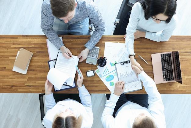 デスクにいるビジネスマンは契約書に署名し、お互いを揺さぶる。中小企業