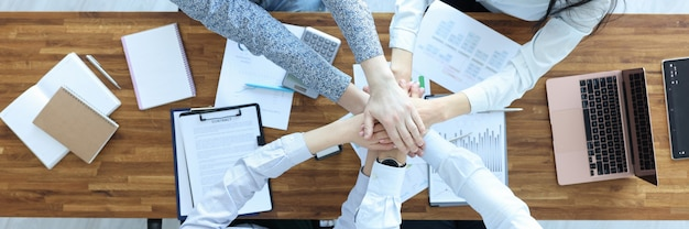 Businessmen and businesswoman at working table hold their hands together partnership agreements