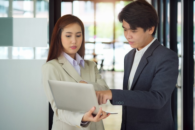 Businessmen and businesswomen chat with each other and use computers to check company budgets.
