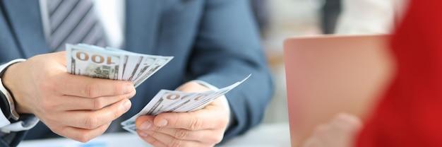 Бизнесмены, считающие наличные долларовые купюры в офисе крупным планом, концепция коррупции и взяточничества
