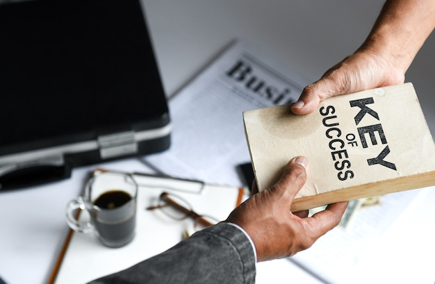 Businessmen deliver key of success book, business concepts.