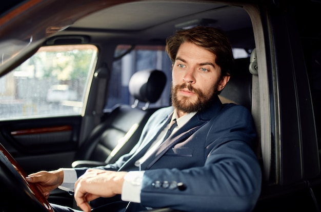 電話で車の旅の贅沢なライフスタイルのコミュニケーションを運転するビジネスマン。高品質の写真
