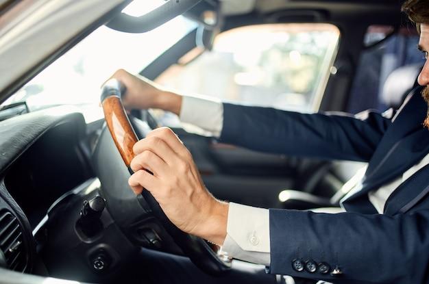 電話で車の旅の贅沢なライフスタイルのコミュニケーションを運転するビジネスマン