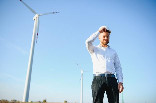 Бизнесмены, занимающиеся проектированием, стоя с красивой улыбкой перед турбиной, глядя в сторону