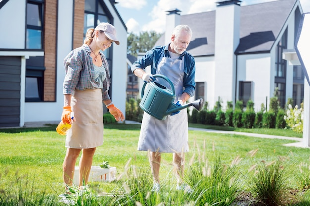 Businessmen in garden. couple of businessmen feeling joyful and relieved while taking care of their garden together