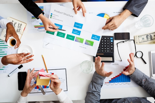 Руки бизнесменов на белом столе с документами и проектами