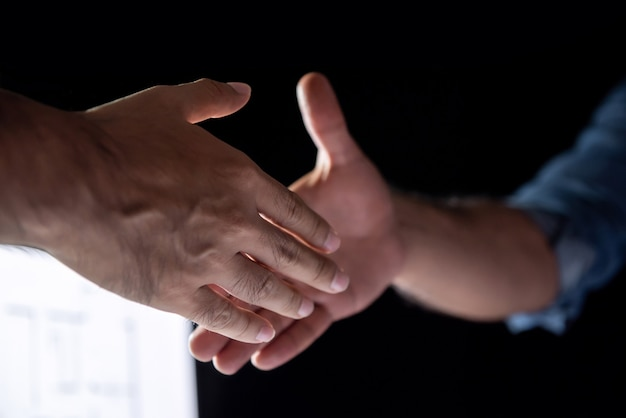 Businessmen handshaking late night in the office