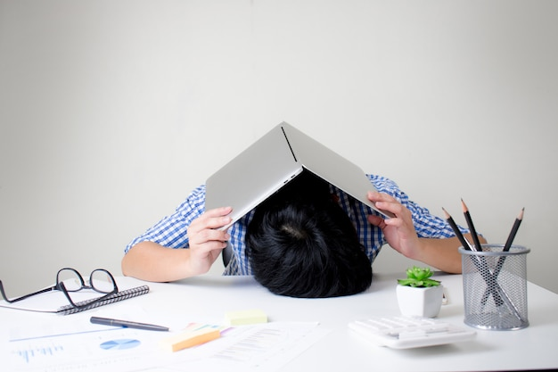Businessmen have a stressful headache from hard work and use a laptop to cover his head.