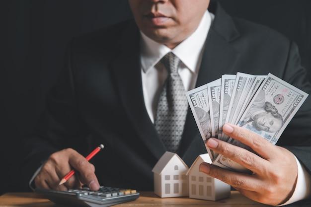 사업가들이 달러 지폐를 들고 계산기를 사용하여 주택 융자 할부를 계산합니다.