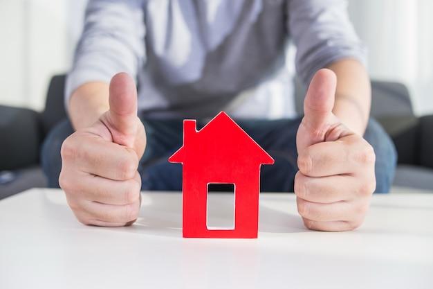 Бизнесмены держат модель дома в руке