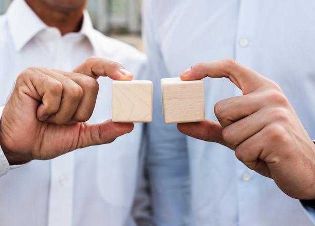 Businessmen holding cubes close-up