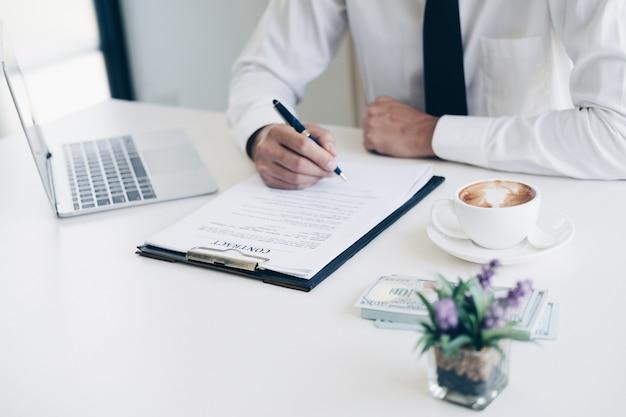 ビジネス文書と契約書を書くペンを持っているビジネスマン
