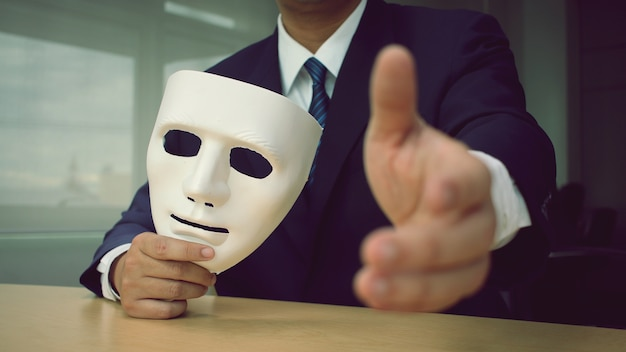 Предприниматели, холдинг белая маска и рукопожатие друг друга на столе.