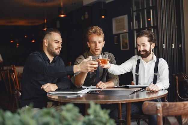 협상에있는 실업가. 테이블에 앉아 알코올을 가진 남자입니다. 친구들이 이야기하고 있습니다.