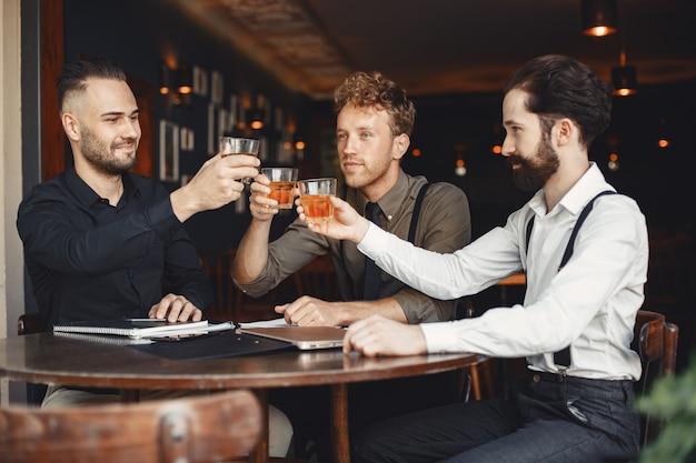 Бизнесмены на переговорах. мужчины с алкоголем сидят за столом. разговаривают друзья.