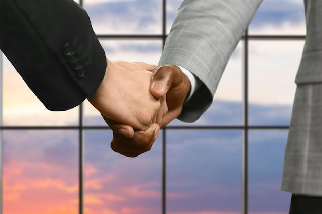 スーツを着たビジネスマンが握手します。日没時のリーダーの握手。常に自然に行動します。国際貿易協定。