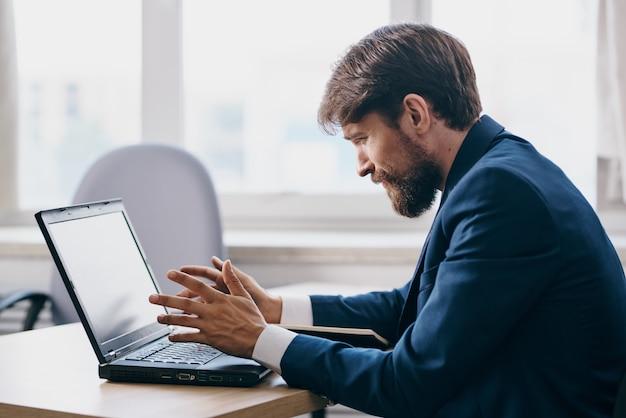 ノートパソコンのキャリアオフィシャルの前のデスクのオフィスのビジネスマン。高品質の写真