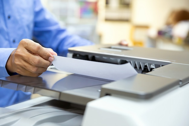 ビジネスマンは、コピー機に紙をセットし、オフィスで印刷、スキャン、ドキュメント用紙の取り出しのためにコピー機またはプリンターを使用します。