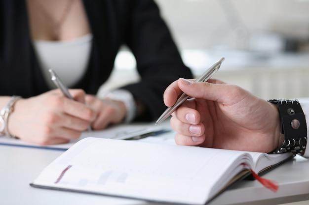 Businessmen make notes in notepad