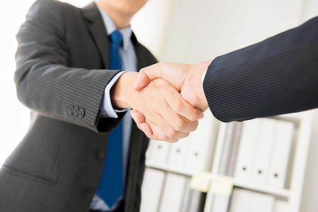 Businessmen making handshake in the office