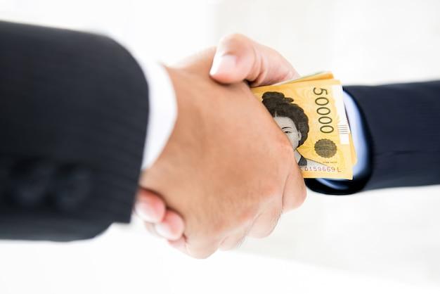 Businessmen making handshake with money, south korean won banknotes, in hands