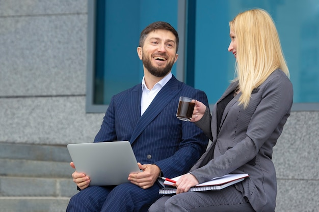 Businessmen man and woman sitting on the stairs