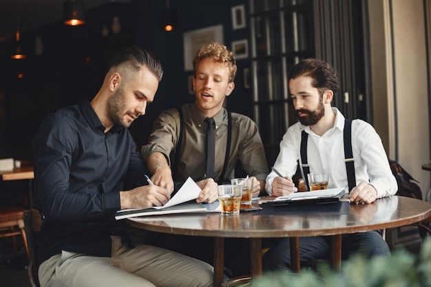 Uomini d'affari nelle trattative. uomini con alcol seduti al tavolo. gli amici stanno parlando.