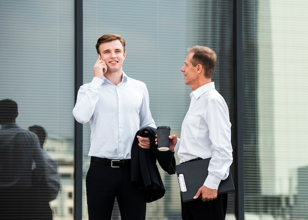 Businessmen outside of glass building